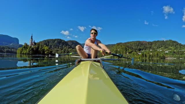 pov stern view of a male athlete rowing in a coxless pair - canottaggio senza timoniere video stock e b–roll