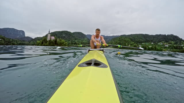 pov stern view of a male athlete rowing on a lake in a coxless four - canottaggio senza timoniere video stock e b–roll
