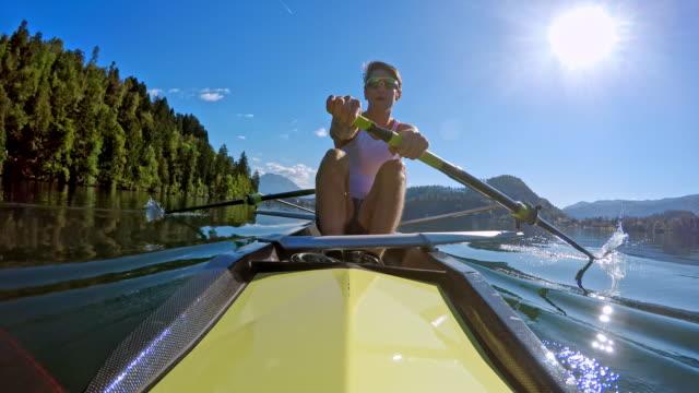 pov stern view of a male athlete rowing with his team mate in sunshine - canottaggio senza timoniere video stock e b–roll