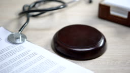 Stethoscope on table, gavel striking on sound block, injury compensation, crime