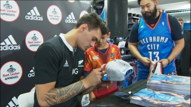 Steven Adams meeting with fans while wearing New Zealand All Blacks jersey at publicity event at Foot Locker retail store in 2014