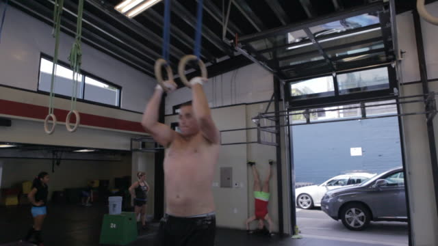 steven makes and attempt, fails; makes another attempt and performs a muscle-up. - 自重トレーニング点の映像素材/bロール