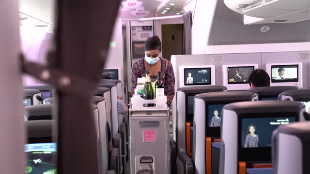 stewardess in face mask serving food in airbus se a380 temporary restaurant. singapore airlines opened up airbus se a380 as temporary restaurants,... - crew stock videos & royalty-free footage