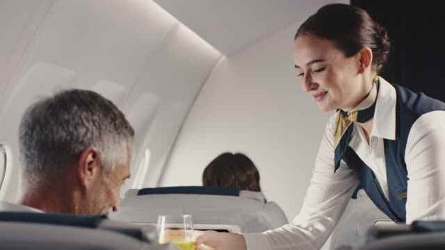 stewardess offering lunch to businessman in jet - air stewardess stock videos & royalty-free footage