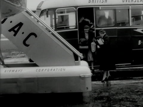 A stewardess watches as passengers disembark an airport bus and start to board an aircraft