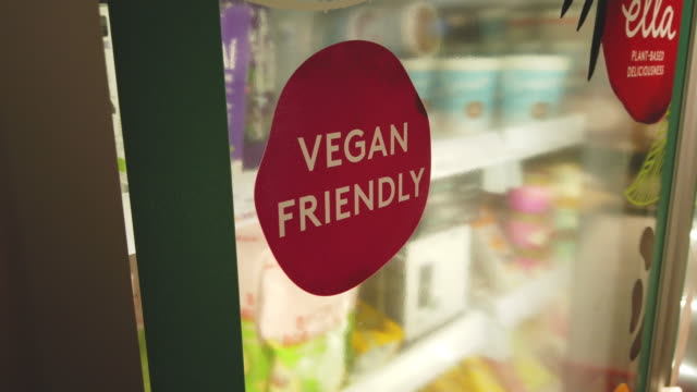 sticker advertising vegan-friendly food is seen on a fridge door in a branch of the planet organic healthfood store on january 03, 2020 in london,... - vegan food stock videos & royalty-free footage