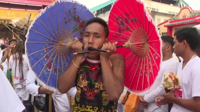 sticking samurai swords umbrellas and even boats through their cheeks devotees of thailand's vegetarian festival go all out during an annual event... - samurai stock videos & royalty-free footage