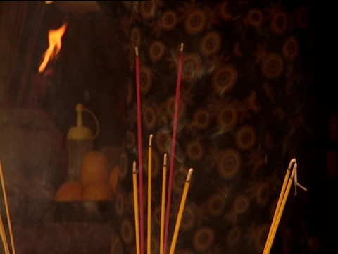 stockvideo's en b-roll-footage met sticks of incense burning worshippers pass behind hong kong - gelovige