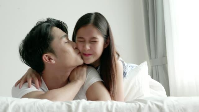 vídeos de stock e filmes b-roll de stiff shoulder with girlfriend massage and kissing at home - dor no pescoço