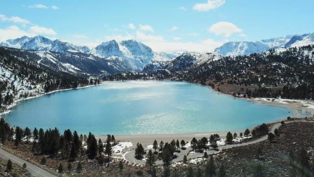 Still Blue Lake with Road and Snowy Mountains