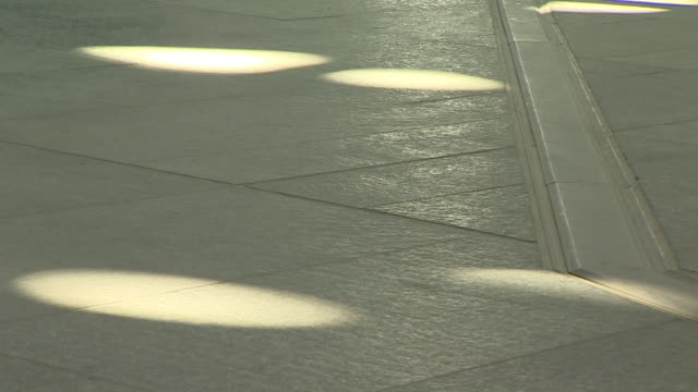 vidéos et rushes de still close up shot of slow moving sunspots hitting the tiled ground of the louvre abu dhabi - carrelage