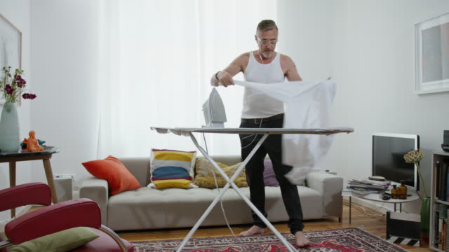 still in shape and good looking tattooed active senior single man in his early 60s with greying hair, grey beard and eyeglasses wears black suit trousers and a tank top while ironing his white shirt himself. - hausdekor stock-videos und b-roll-filmmaterial