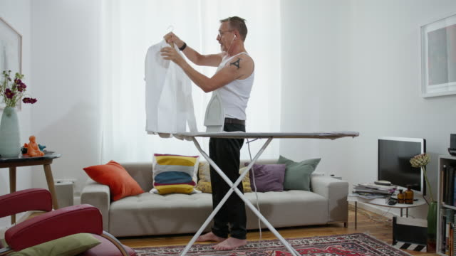 still in shape and good looking tattooed active senior single man in his early 60s with greying hair, grey beard and eyeglasses wears black suit trousers and a tank top while ironing his white shirt himself. - oberhemd stock-videos und b-roll-filmmaterial