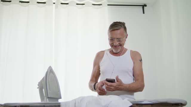 still in shape and good looking tattooed active senior single man in his early 60s with greying hair, grey beard and eyeglasses wears a tank top while ironing his white shirt himself. - strykjärn bildbanksvideor och videomaterial från bakom kulisserna