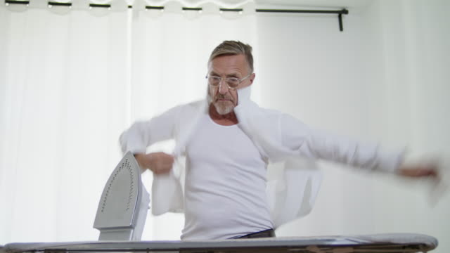Still in shape and good looking tattooed active senior single man in his early 60s with greying hair, grey beard and eyeglasses wears a tank top while ironing his white shirt himself.