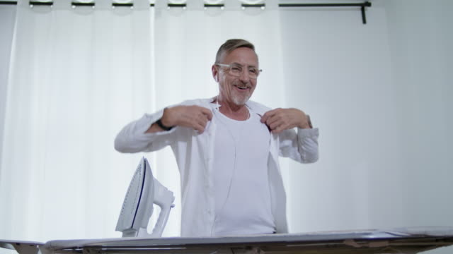 still in shape and good looking tattooed active senior single man in his early 60s with greying hair, grey beard and eyeglasses wears a tank top only while ironing his white shirt himself. - lavori di casa video stock e b–roll