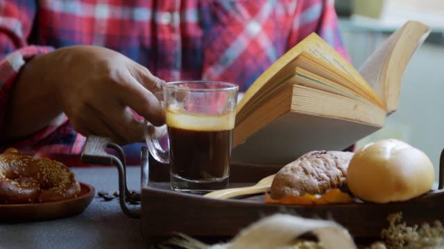 vídeos de stock e filmes b-roll de still life details,senior man relaxing and reading book drinking coffee - ler
