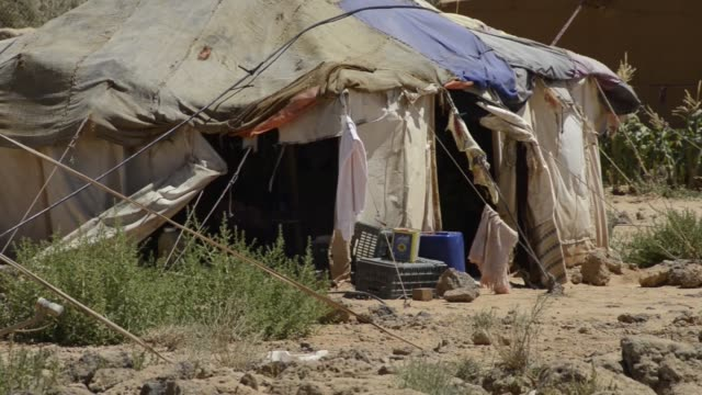 still on large refugee tent clothes blowing in wind in desert in jordan - シリア難民問題点の映像素材/bロール