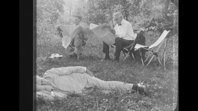 Still photo from 1921 Maryland camping trip group shot of Thomas Edison and other people sitting outdoors on chairs in front of group of people...