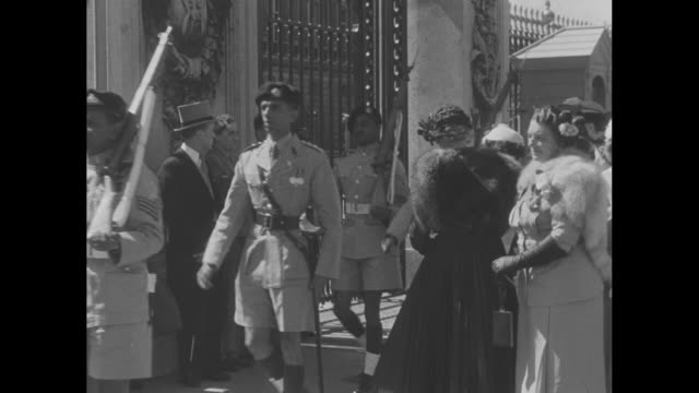 still photo of queen elizabeth in tiara / navy officers walking by fountain at buckingham palace / native riflemen marching through crowd / crouching... - tiara stock videos & royalty-free footage