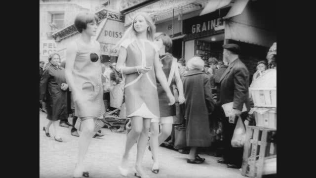 Still photographs of French models in mod style designs / line of models in a Paris clothing store showing the rising hem line / models dance down...