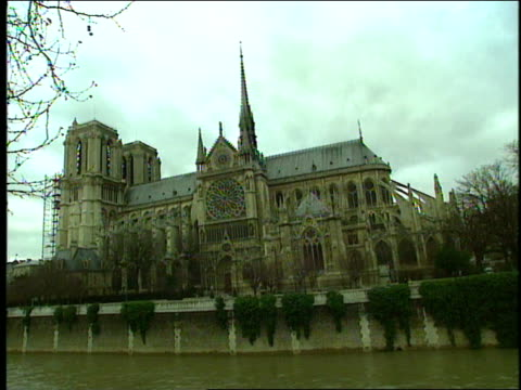 stockvideo's en b-roll-footage met a still pond reflects the gothic notre dame cathedral. - kerktoren