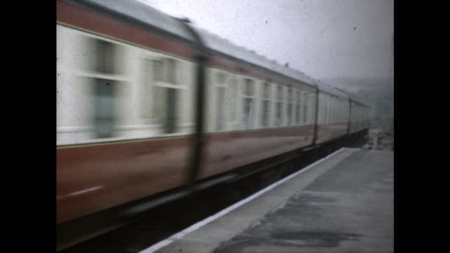 still shot from a train station platform; train approaches and passes the camera - colour image stock videos & royalty-free footage