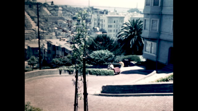 still shot from top of lombard street in san francisco man on red threewheeled motorcycle riding down the hill city view in the background - lombard street san francisco stock videos & royalty-free footage