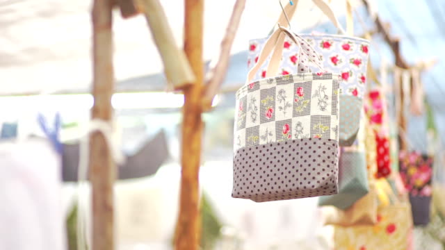 cu still shot : hanging multi colored quilted bags on s-shaped hook at the traditional street market with blurred background. - patchwork stock videos & royalty-free footage