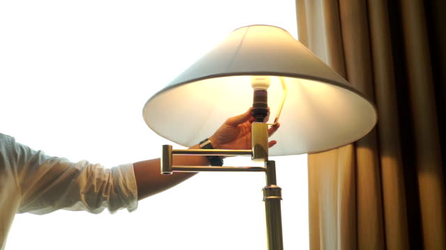 "ms still shot : man's hand is switched ""off"" and ""on"" on a stand lamp in the room. - electric lamp video stock e b–roll"