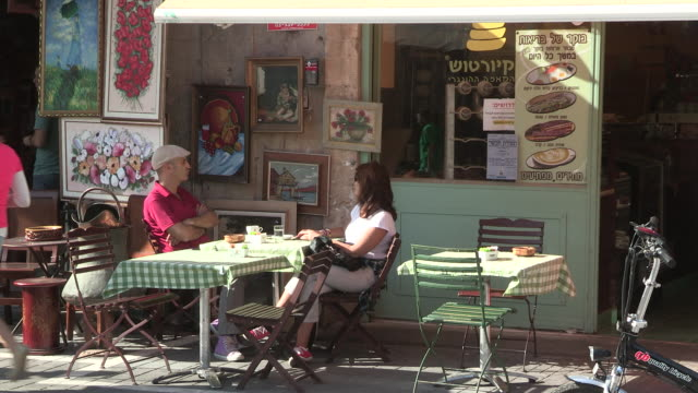 still shot of a couple sitting outside an old town cafe - jaffa stock-videos und b-roll-filmmaterial