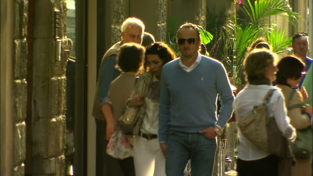 still shot of a couple walking near shops in late afternoon. - italian culture stock videos & royalty-free footage