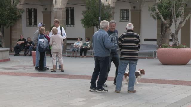 vídeos y material grabado en eventos de stock de still shot of a few men with a small dog. - plaza