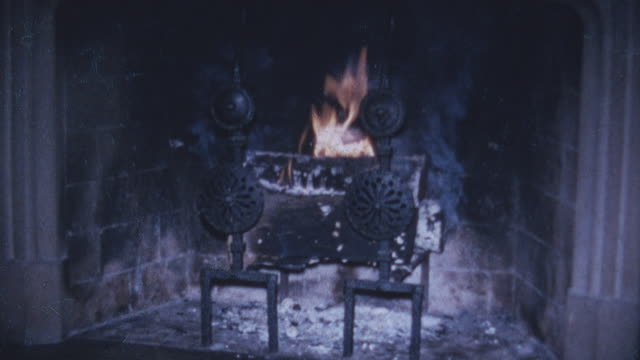 still shot of a fireplace with a fire burning inside ashes at the bottom of the fire - burning stock-videos und b-roll-filmmaterial
