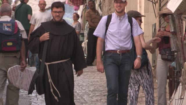 still shot of a franciscan monk walking with another man. no audio - 聖地パレスチナ点の映像素材/bロール