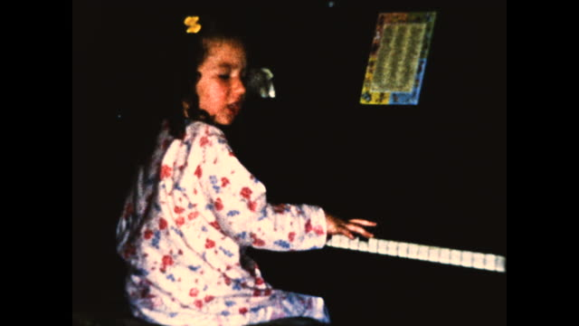 still shot of a girl in pajamas playing the piano - only girls stock videos & royalty-free footage