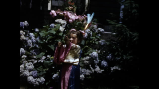 still shot of a little girl wearing a pink kimono; she holds flowers branch in one and fishing rod with fake fish in the other; flower bush in the... - only girls stock videos & royalty-free footage