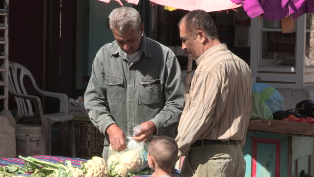 still shot of a man and child buying cauliflower. - 聖地パレスチナ点の映像素材/bロール
