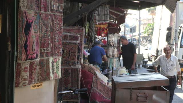 still shot of a man at a small old town rug shop - jaffa stock-videos und b-roll-filmmaterial