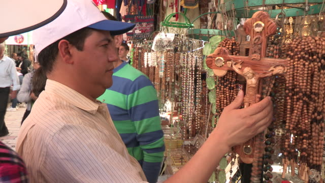 still shot of a man looking at rosaries - baseballmütze stock-videos und b-roll-filmmaterial