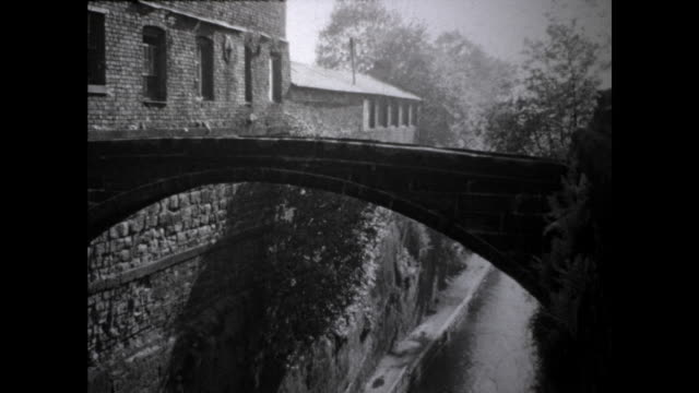 still shot of a narrow bridge on top of a narrow creek in the city buildings and trees on the side - narrow stock videos & royalty-free footage