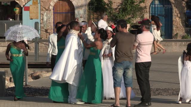 still shot of a small wedding celebration in the harbor - jaffa stock-videos und b-roll-filmmaterial