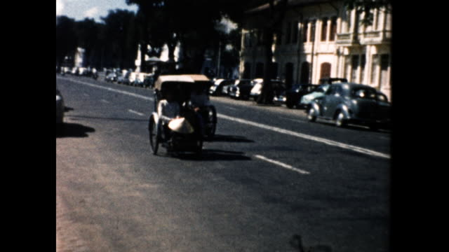 still shot of a street in asia; two pedicabs driving toward the camera; one passenger holding a straw hat - straw hat stock videos & royalty-free footage