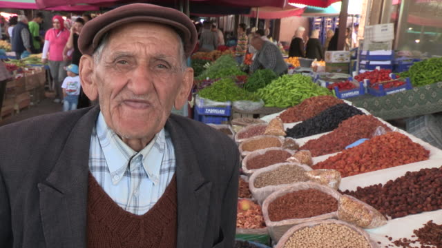 Still shot of a very old man in front of spices NO