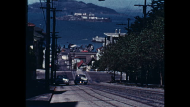 still shot of a white car driving uphill, bay and island in the background - hill stock videos & royalty-free footage