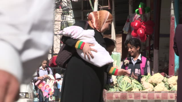 still shot of a woman holding a baby while looking at produce. - single mother stock videos & royalty-free footage