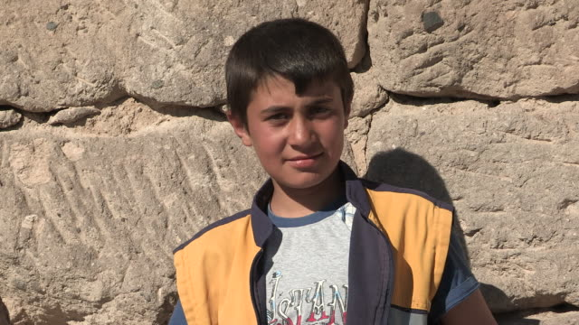 still shot of a young boy in front of a stone wall no - only boys stock videos and b-roll footage