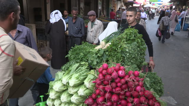 still shot of a young man with a produce cart in the middle of a busy pedestrian street. - crucifers stock-videos und b-roll-filmmaterial