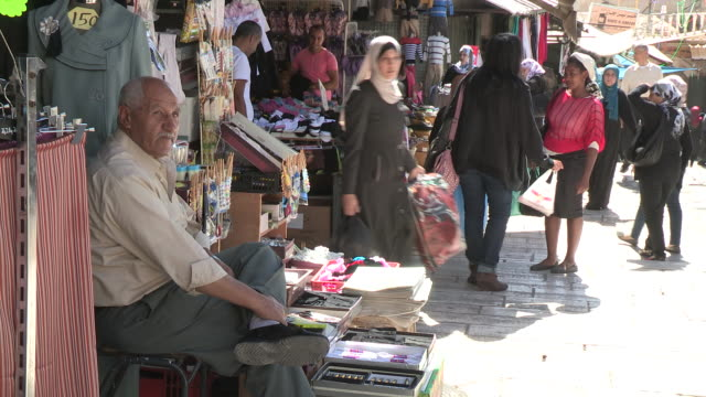 still shot of an old man sitting in front of his wares. no audio - 僧衣点の映像素材/bロール