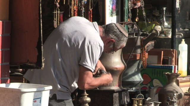 stockvideo's en b-roll-footage met still shot of an old town shop owner cleaning his wares on the sidewalk - jaffa